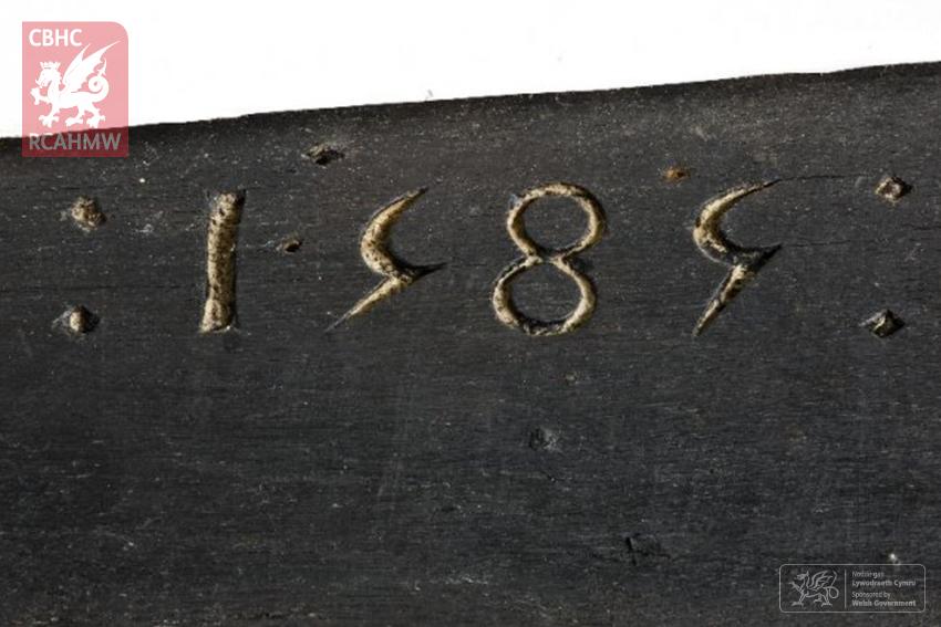 Yr arysgrif 1585 yn Uwchlaw'r–coed.