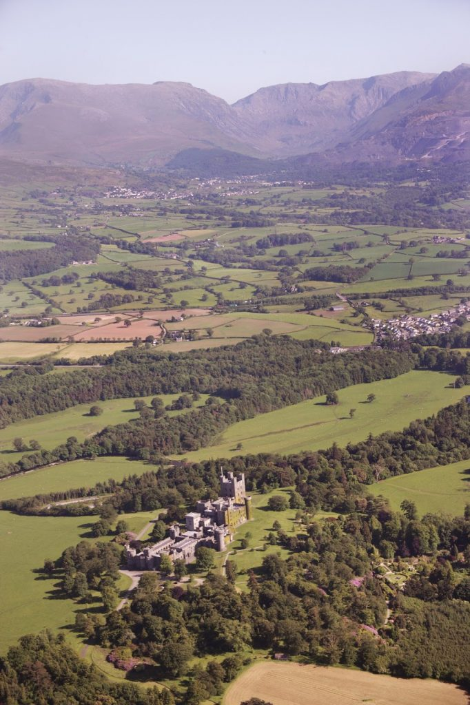 Penrhyn Castle and its parkland, with Bethesda and Penrhyn quarry in the middle distance.  The neo–Norman castle was built in the nineteenth century and was the home of Lord Penrhyn, owner of Penrhyn quarry. NPRN: 16687