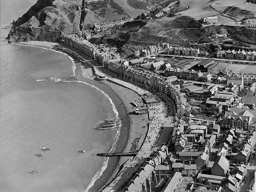 Llun o Aberystwyth yn dangos glan y môr a'r dref yn yr haf, 1932, Casgliad Aerofilms. Cyf. Cat. WPW040024, NPRN 33035.