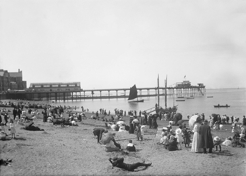 Black and white image dating from c.1910 showing a busy beach scene at Aberystwyth with the Pier in the background.