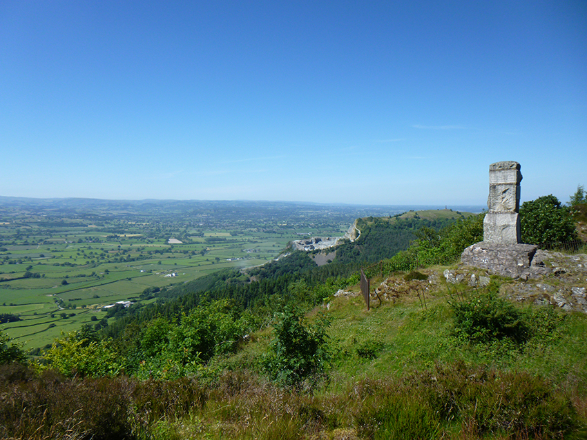 Romany Monument to Ernest Burton looking north, with Criggion Quarry and Rodney's Pillar visible in the background, and the Severn Valley below.