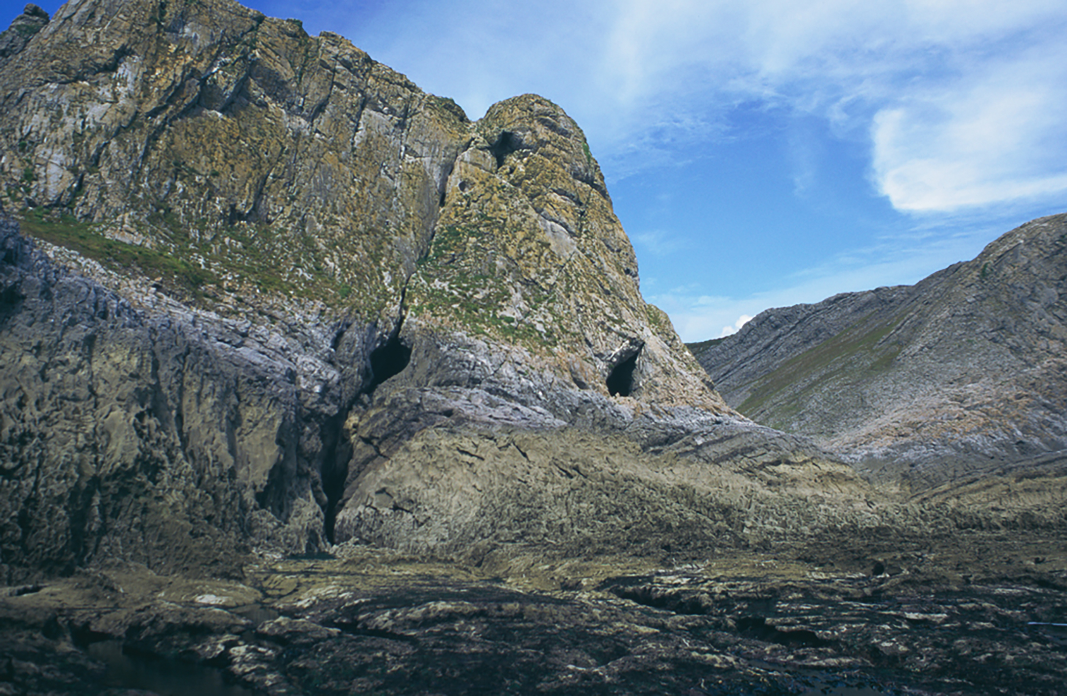 Paviland Cave or Goat's Hole at low tide. The elongated fissure of the cave is at centre-right. The cliffs would have looked out over fertile lowland plains.