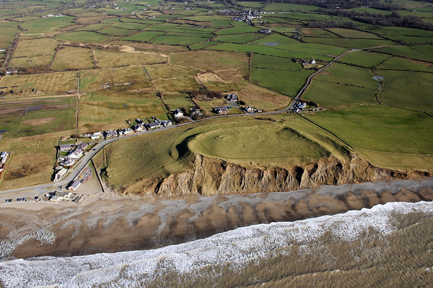 Dinas Dinlle coastal fort is owned by the National Trust. It is set on a hill of glacial drift sediments overlooking the sea and Caernarfonshire coastal plain. The fort is protected as a Scheduled Monument whilst the hill itself is a Site of Special Scientific Interest, designated for the geological importance of glacial sediments. (Crown Copyright: RCAHMW AP_2014_0877)