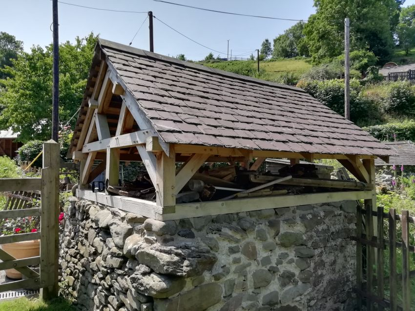 The completed timber-framed log store with stone plinth