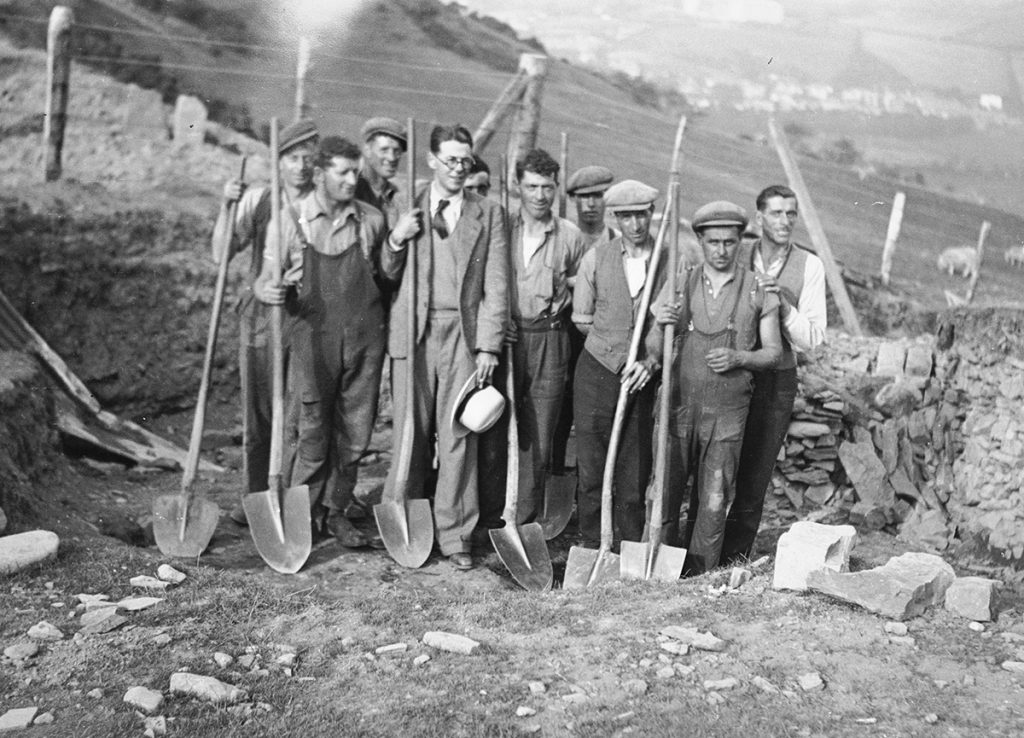 Yr Athro Daryll Forde ifanc (canol, gyda het) a gweithwyr lleol yn cloddio Porth y Culdir ym mryngaer Pen Dinas ym 1934 (Hawlfraint y Goron CBHC).